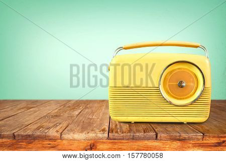 Retro radio on table with vintage green eye light background - old technology