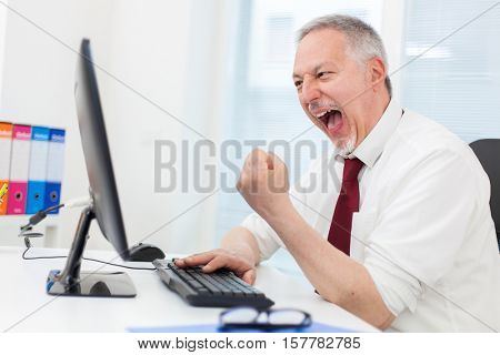 Very happy businessman looking at his computer monitor