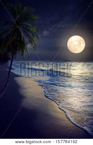 Beautiful fantasy tropical beach with Milky Way star in night skies full moon - Retro style artwork with vintage color tone (Elements of this moon image furnished by NASA)