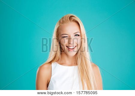 Close up portrait of a smiling blonde woman winking and looking at camera isolated on the blue background