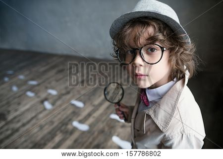 Little detective with a magnifying glass