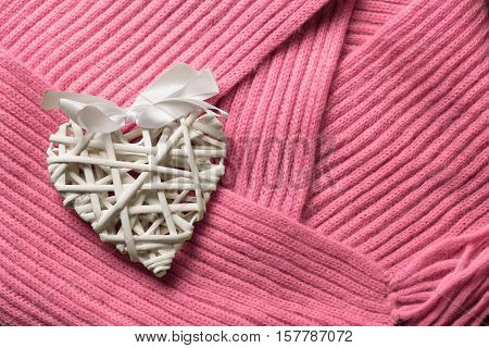 Beautiful white handmade wattled from rattan wooden valentine's day heart decoration with bow lays on pink woollen scarf background. Copyspace.
