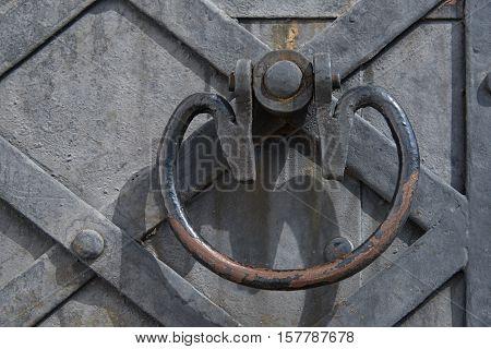 A fragment of an old wooden door with metal handle. Door strengthening iron strips. Texture background