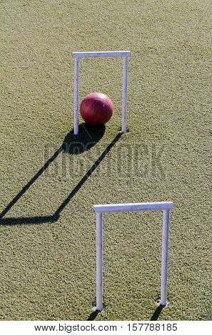 Close up of red croquet ball and hoop