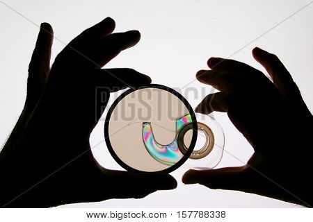 Silhouettes of hands with a polarizing filter, followed by the plastic part - adhesive tape on white background computer display