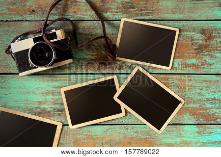 Retro camera and empty old instant paper photo album on wood table - blank photo frame vintage style