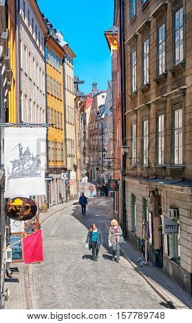 STOCKHOLM, SWEDEN - APRIL 14, 2010: People walk on Osterlanggatan Street in Gamla Stan (Old Town) not far from Saint George and the Dragon Statue. The Gamla Stan is historical part of the capital.