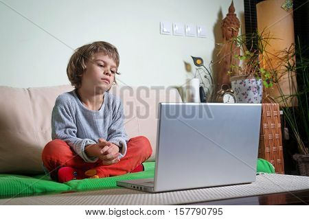 Little boy on sofa bored by watching cartoons on laptop.