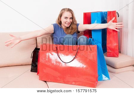 Woman Sitting On Couch With Shopping Bag Around Acting Joyful