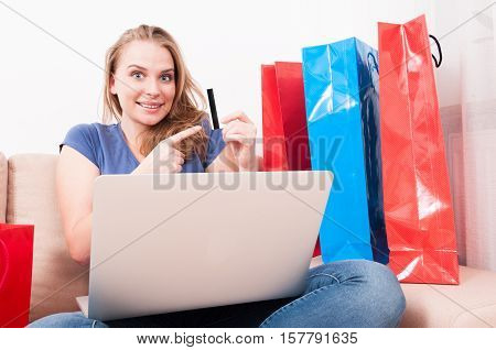 Woman Sitting On Couch Holding Laptop Pointing Card