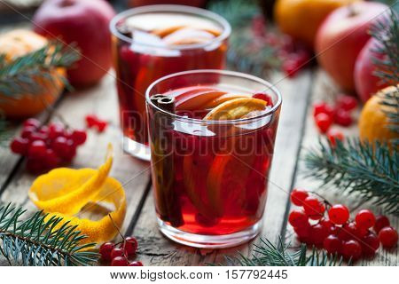 Winter warm drink. Homemade mulled wine or sangria with orange slices, cranberries, cinnamon and anise on wooden table. Closeup. Christmas tree decorations