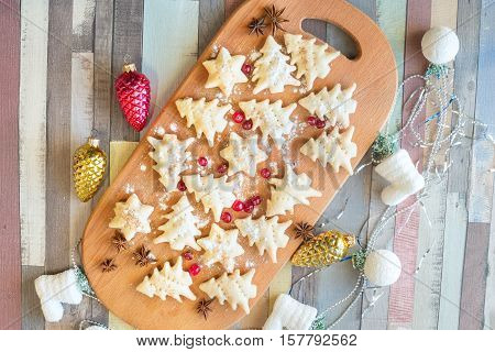 Festive cookies prepared for Christmas sprinkled with powdered sugar with spices and cranberries lying on a wooden table among the Christmas-tree decorations. Top view.