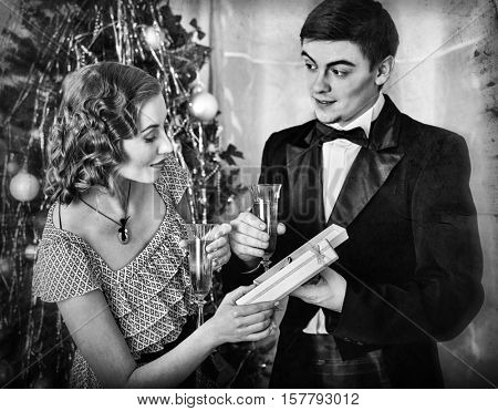 Couple with champagne glass on party near Christmas tree. Jewelry box with bijouterie. Retro style.
