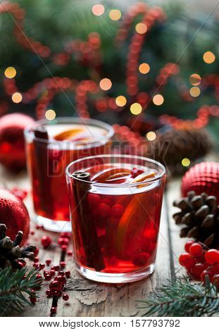 Winter warm drink. Christmas hot cranberry tea, orange pomegranate punch or mulled wine in a rustic wooden table. Closeup. Christmas tree decorations with pine cones.