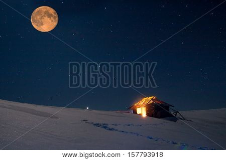 Winter landscape with a starry sky and the full moon. The light in the cabin in the mountains