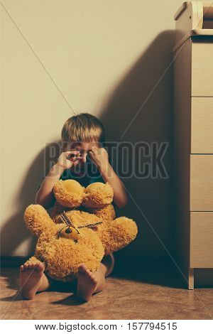Little scared boy sitting in corner with toy bear and crying. Child abuse.