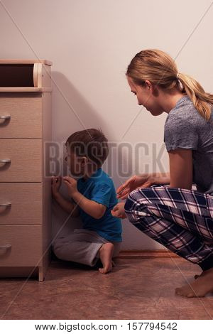 Young caucasian woman comforting her little son after quarrel and punishment. Boy is sitting in corner. Child abuse.