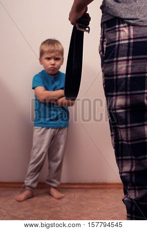 Angry boy and abusive mother with belt. Child abuse. Domestic violence aggression in the family.