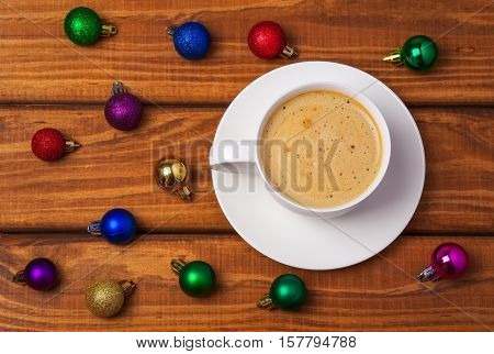Cup of coffee and different christmas bubbles on wooden background.