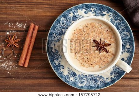 Masala tea chai latte traditional hot Indian sweet milk with spices, cinnamon stick, herbs blend organic infusion healthy beverage in porcelain cup on wooden table background