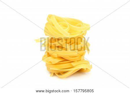 Raw fettuccine pasta isolated on white background.
