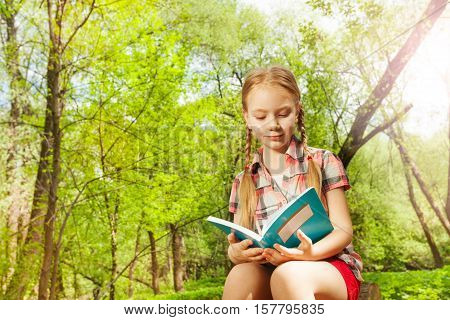 Close-up portrait of adorable ten years old girl reading a book in the park at sunny day