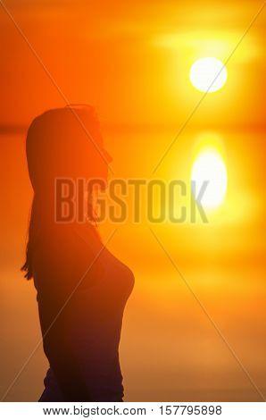 Beautiful female model enjoying sunsetat seaside. Calm water of salt lake Elton reflects silhouette of woman. Sun goes under horizon. Girl stands alone in water. Sun reflects in Elton's water.