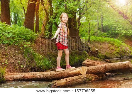 Portrait of happy young girl crossing a river through a log bridge in the forest