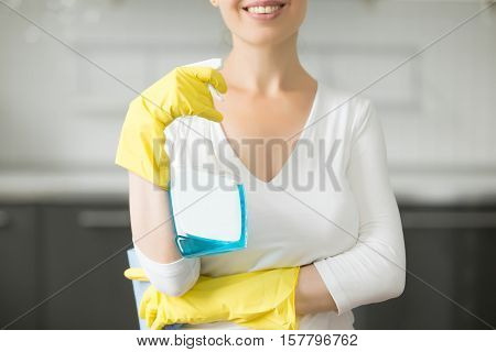 Close up of a smiling attractive young woman, wearing rubber protective yellow gloves, holding rag and spray bottle detergent. Home, housekeeping concept