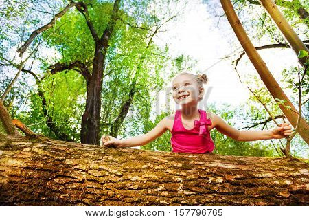 Portrait of cute little girl peeping behind fallen tree in summer park