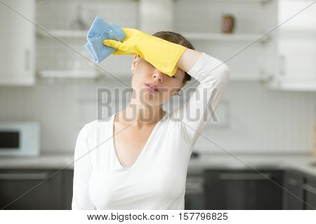 Tired and exhausted woman, frustrated with doing much work about the house resting for a minute or wiping her forehead after finishing work. Home, housekeeping concept
