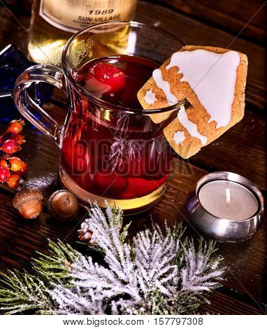 Still life of winter hot drink mulled and spruce branch. Warming mulled wine with cookie in form of house. Top view.