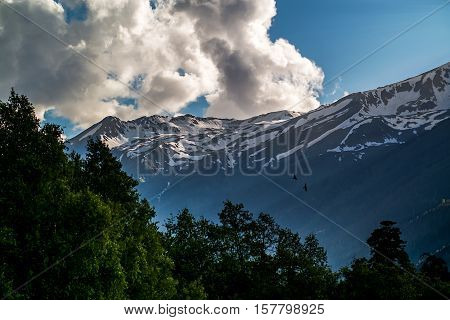 the snow-capped mountain peaks covered with forest against the blue sky