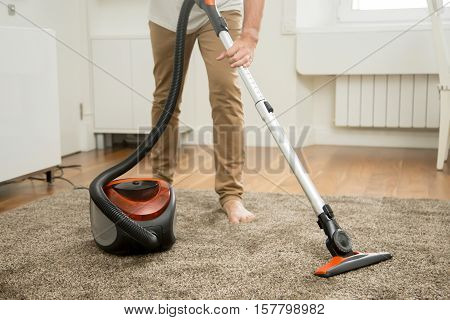 Close up of man vacuum cleaning the carpet in the living room, modern scandinavian interior. Busy, cleaning day. Home, housekeeping concept.