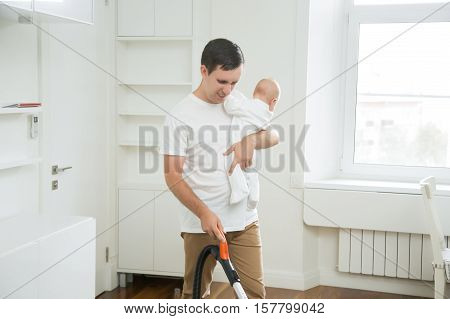 Frustrated stay-at-home dad unsatisfied with his role, doing vacuum cleaning the carpet in the living room holding a baby in one hand and vacuum cleaner in another. Home, housekeeping concept
