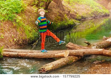 Portrait of cute seven years old boy crossing the river in summer