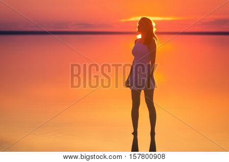 Beautiful female model stands in front of the sun under sunset at seaside. Calm water of salt lake Elton reflects silhouette of woman. Sun goes under horizon. Girl stands alone in water.
