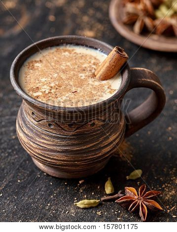 Masala pulled tea chai latte delicious hot Indian sweet milk spiced drink, ginger, fresh spices and herbs blend, anise organic infusion healthy wellness beverage teatime ceremony in rustic clay cup
