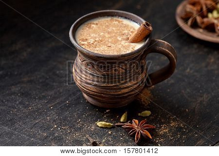 Milk tea chai latte traditional tasty refreshing morning breakfast organic healthy hot beverage drink with natural aroma spices blend, cardamon, anise, cinnamon, in rustic ceramic cup
