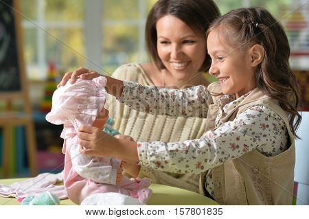 Portrait of happy mother and her cute daughter play with baby doll together