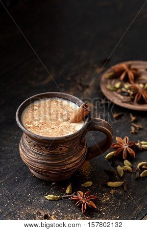 Milk tea chai latte traditional tasty refreshing morning breakfast sweet organic healthy hot beverage drink with natural aroma spices blend, cardamon, anise, cinnamon, in rustic ceramic cup