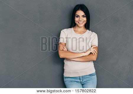 Confident and beautiful. Attractive young woman in casual wear keeping arms crossed and looking at camera with smile while standing against grey background