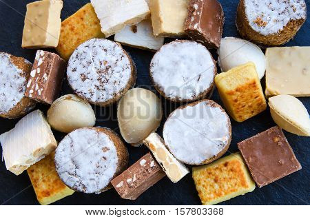 Different Spanish sweets consumed at Christmas: polvoron or shortbread turron or almond nougat.Top view.
