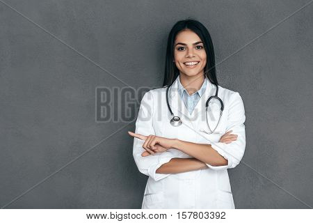 Doctor pointing copy space. Attractive young female doctor in white lab coat keeping arms crossed and smiling while standing against grey background