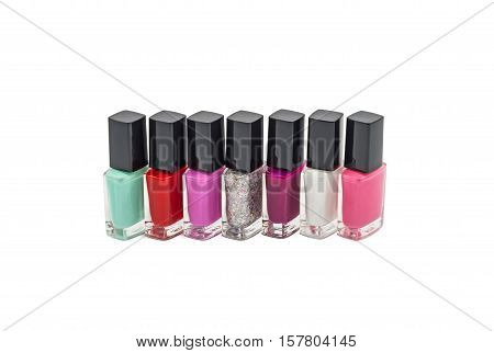 Multi-colored bottles with nail polish laid out on a white background