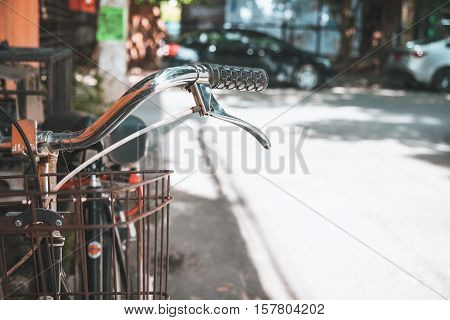 Detail of a vintage bicycle handlebar parked in the urban narrow street (vintage color tone styles)