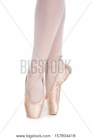 The close-up of ballerina in pointe shoes posing on a white background