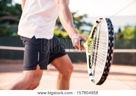 Man playing in tennis on court. cropped image