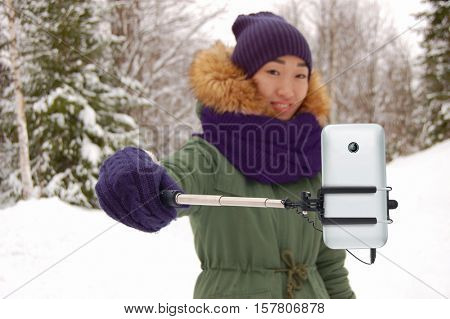 Asian woman with selfie stick at winter outdoors