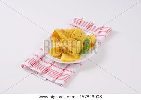 plate of empty folded pancakes on checkered dishtowel